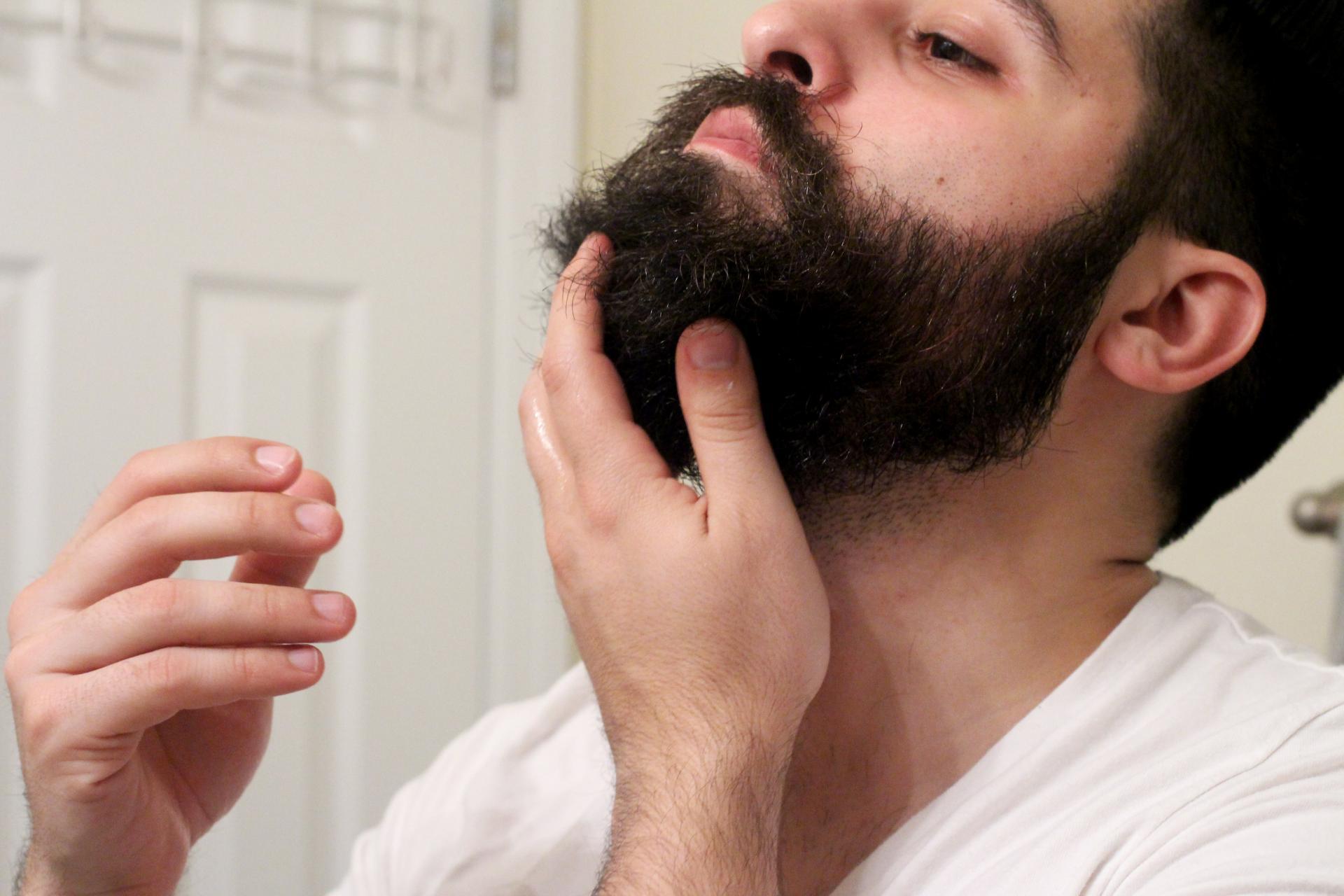 мужчина мажет бороду маслом