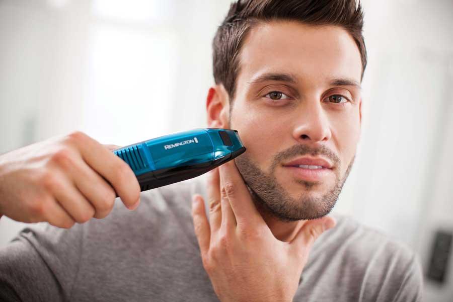 мужчина стрижется триммером для бороды
